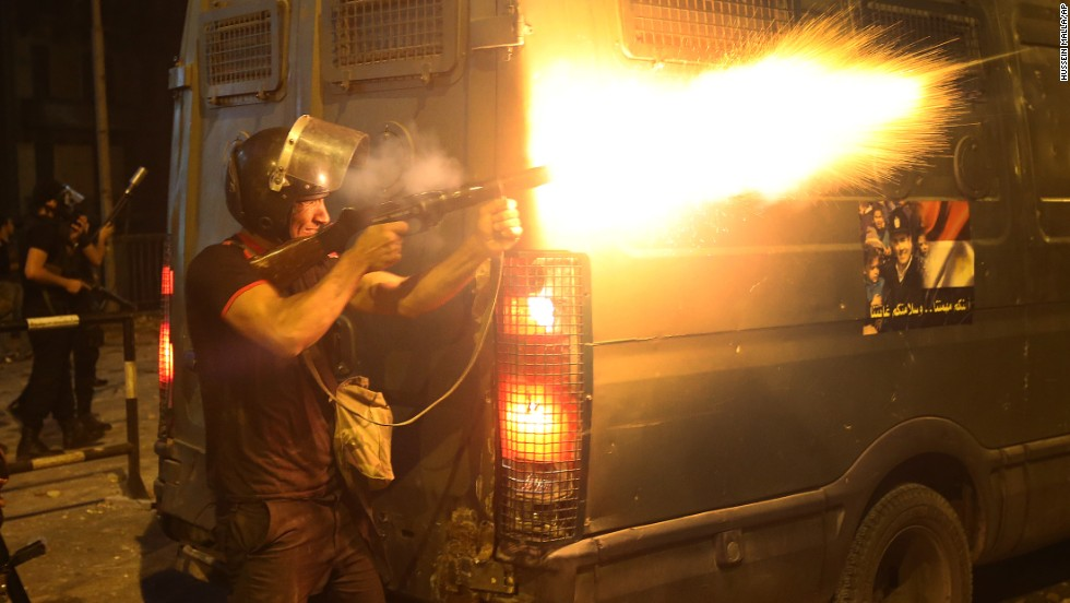 A riot police officer fires tear gas toward Morsy supporters during clashes in Cairo on Monday, July 15.