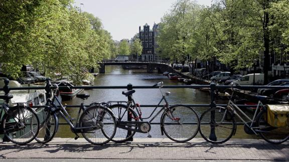 Bicycles are fixed to the railing of a bridge in Amsterdam