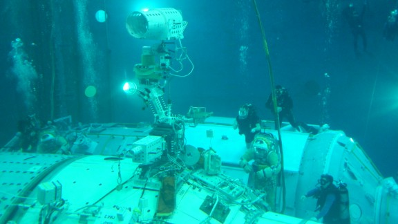 Cosmonauts train in a water tank to install the UrtheCast cameras on a full-scale model of the space station.
