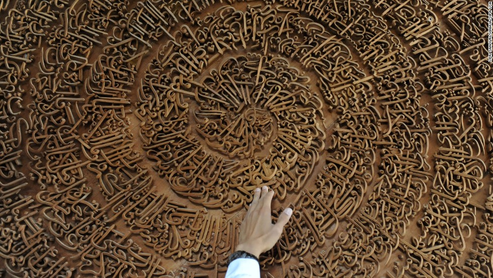 A teacher shows a carving of the Quran at the Islamic Boarding School of Ashriyyah Nurul Iman in Parung, Indonesia, on July 16.