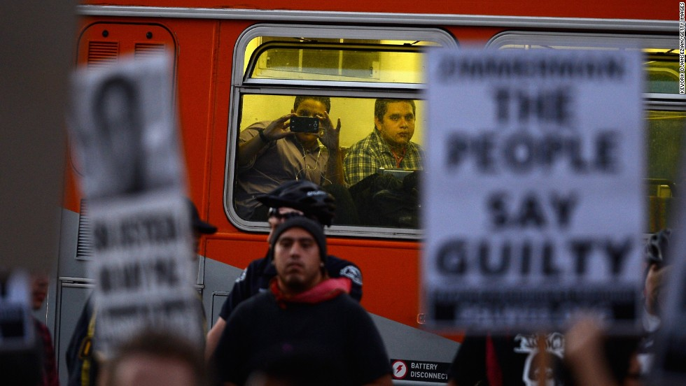 A passenger takes a picture of protesters as he rides a city bus on July 16 in Los Angeles.