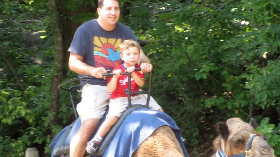 "Full-time dad Lance Somerfeld and his son, Jake, ride the camel at the Bronx Zoo, one of their favorite places to visit. Somerfeld says ""being an active, engaged, involved dad is a cool and rewarding thing to do."" His own father ""never changed a diaper in his life."" (Read his story.)"