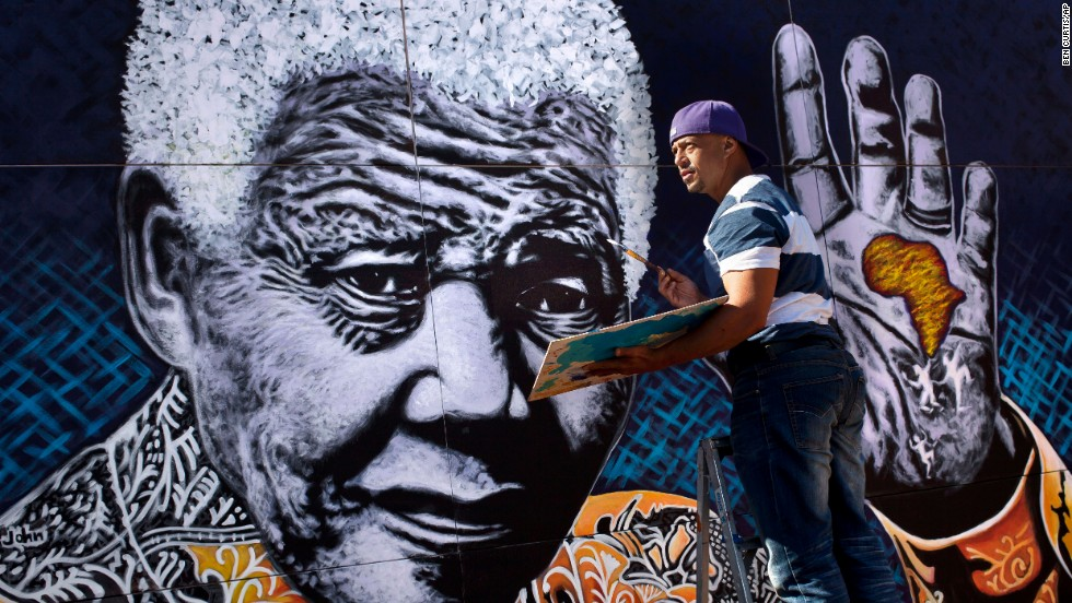 "South African artist John Adams works on a giant painting of <a href=""http://www.cnn.com/2012/12/11/world/africa/nelson-mandela---fast-facts"">Nelson Mandela</a> in a suburb of Johannesburg. Mandela, an anti-apartheid icon and Nobel peace laureate, endured 27 years in prison before becoming South Africa's first democratically elected president. Click through the gallery for other artistic tributes to ""the world's most famous political prisoner."""