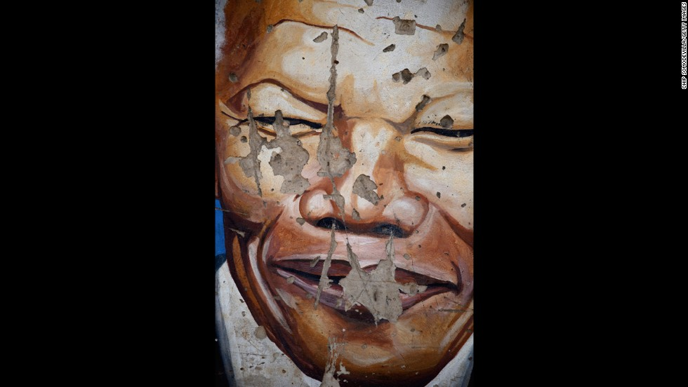 <strong>SOUTH AFRICA: </strong>A mural depicts Mandela near the Regina Mundi Catholic Church in the Soweto Township in Johannesburg. The church played a central role in the anti-apartheid struggle, opening its doors to shelter activists.