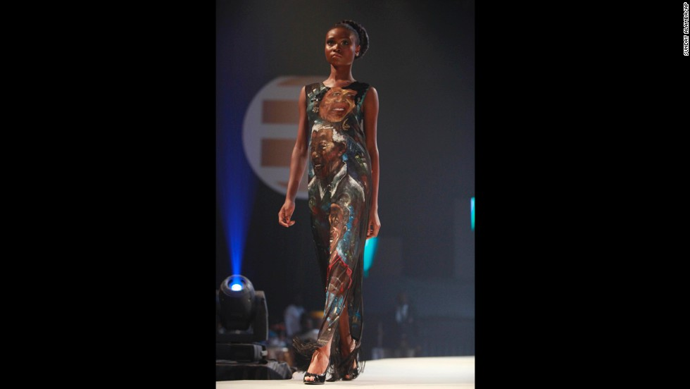 <strong>NIGERIA:</strong> A model displays an outfit by fashion designer Deola Sagoe that features faces of renowned African figures, including Mandela, during the launch of Ebony Life TV in Lagos.