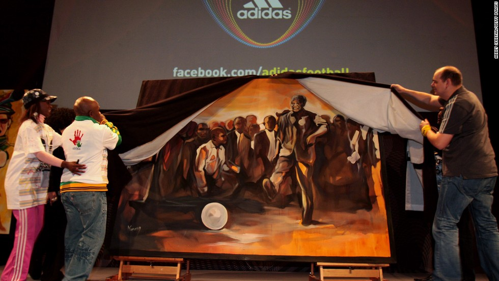 <strong>SOUTH AFRICA:</strong> From left, actress Hlubi Mboya, former boxer Baby Jake Matlala and Thomas van Schaik from Adidas unveil a piece of art during a Live Quest event showcasing paintings of key moments of the 2010 FIFA World Cup at the Adidas Jo'bulani Centre in Johannesburg.