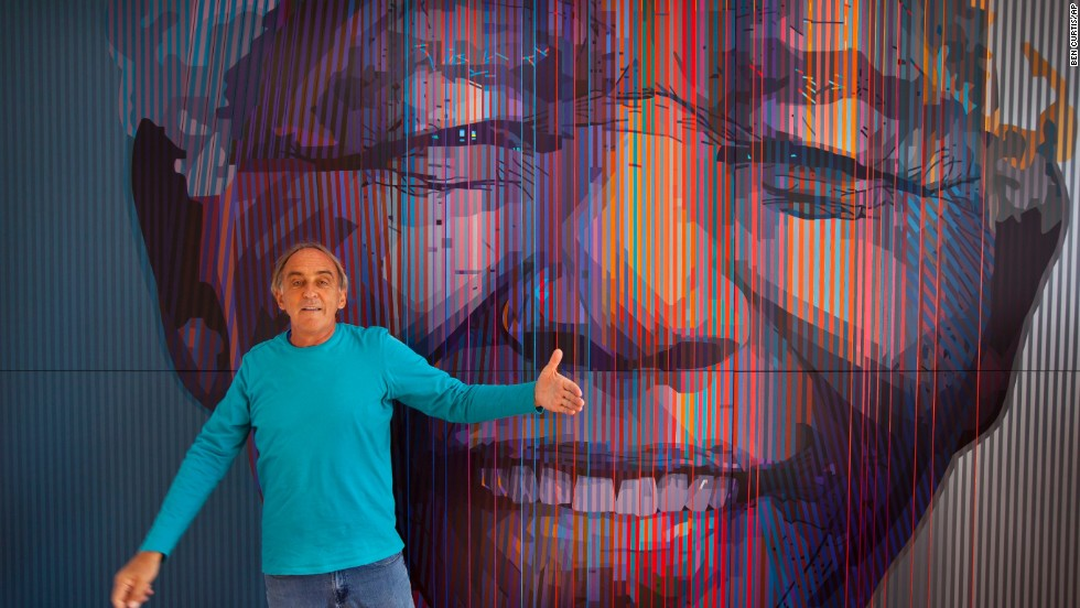 "<strong>SOUTH AFRICA: </strong>South African artist Paul Blomkamp stands in front of the giant acrylic-on-canvas painting he made of Mandela at his studio in Johannesburg. He said he was drawn to Mandela because of his ""exceptional energy."""