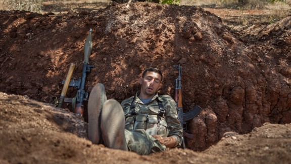 A rebel fighter naps in a trench about 300 feet from the Syrian government forces