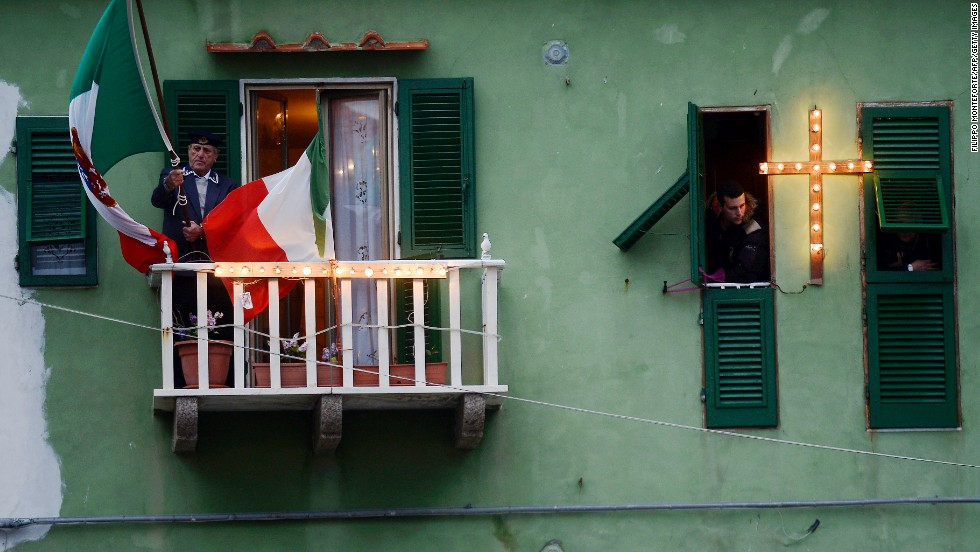 A man holds an Italian flag on his balcony overlooking the port of Giglio on January 13, 2013.