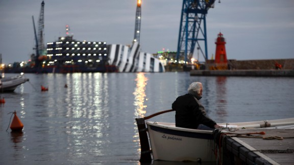 A man sits in his boat in front of the half-submerged cruise ship on January 8, 2013.