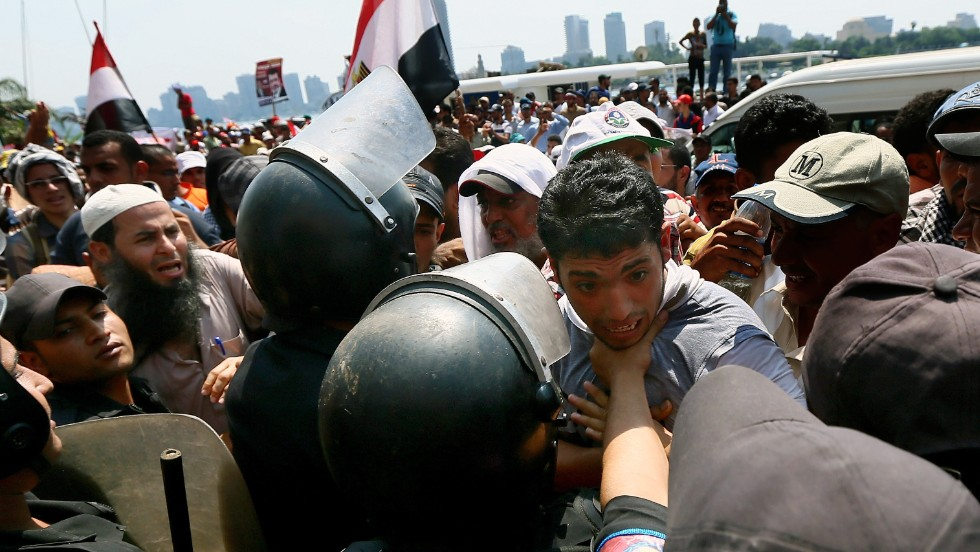 A Morsy supporter is held back by riot police during a rally near Tahrir Square on July 17.