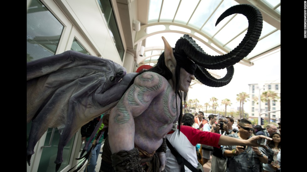 An attendee in an elaborate costume makes his way through a crowd outside the San Diego Convention Center on July 19.