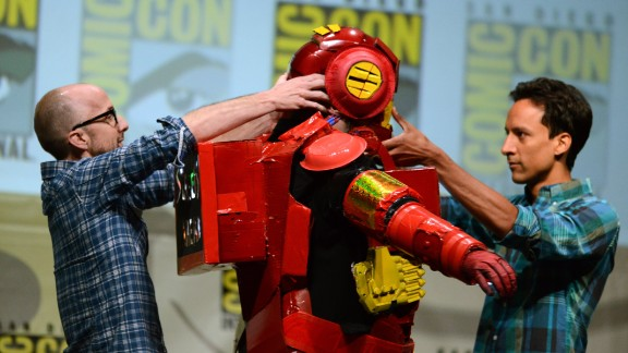 """Dan Harmon, center, creator and executive producer of """"Community,"""" is helped out of a costume by actors Jim Rash, left, and Danny Pudi during the """"Community"""" panel on the final day of Comic-Con International on Sunday, July 21, in San Diego. Running from Wednesday through Sunday, July 21, the event floods the San Diego Convention Center with more than 100,000 attendees as they shuffle between panels promising exclusive previews and answers to fans' burning questions. <a href=""""http://www.cnn.com/2013/07/18/us/gallery/comic-con-2013/index.html"""" target=""""_blank"""">See more sights from Comic Con 2013</a>."""
