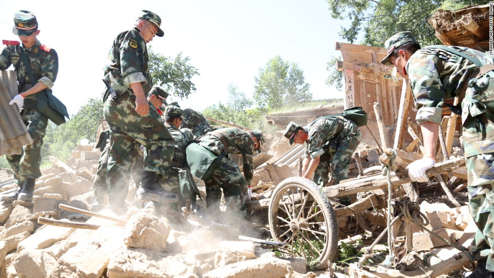 Rescuers look for survivors in the ruins of a house in Hetuo township in Dingxi on July 22. Emergency services are converging on the area, including the Red Cross Society of China, which is sending 200 tents and other supplies to help those left homeless.