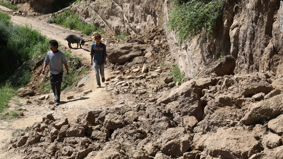 Two men make their way along a damaged road in Hetuo township in Dingxi on July 22.  The original quake and powerful aftershocks caused roofs to collapse, cut telecommunications lines and damaged a major highway linking Gansu Province's capital of Lanzhou to the south, reports say.
