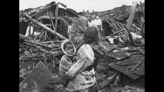 A woman and child wander among debris in Pyongyang, North Korea, after an air raid by U.S. planes, circa 1950. The war began on June 25, 1950, when the North Korean People