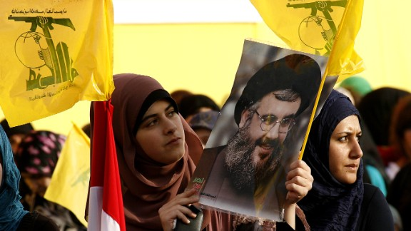 Women hold Hezbollah flags and a picture of the movement