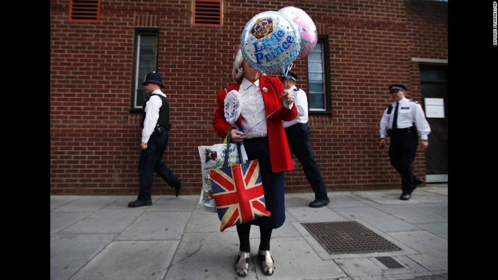 Royal supporter Margaret Tyler holds decorative balloons as she waits outside St. Mary's Hospital in London on Saturday, July 20.