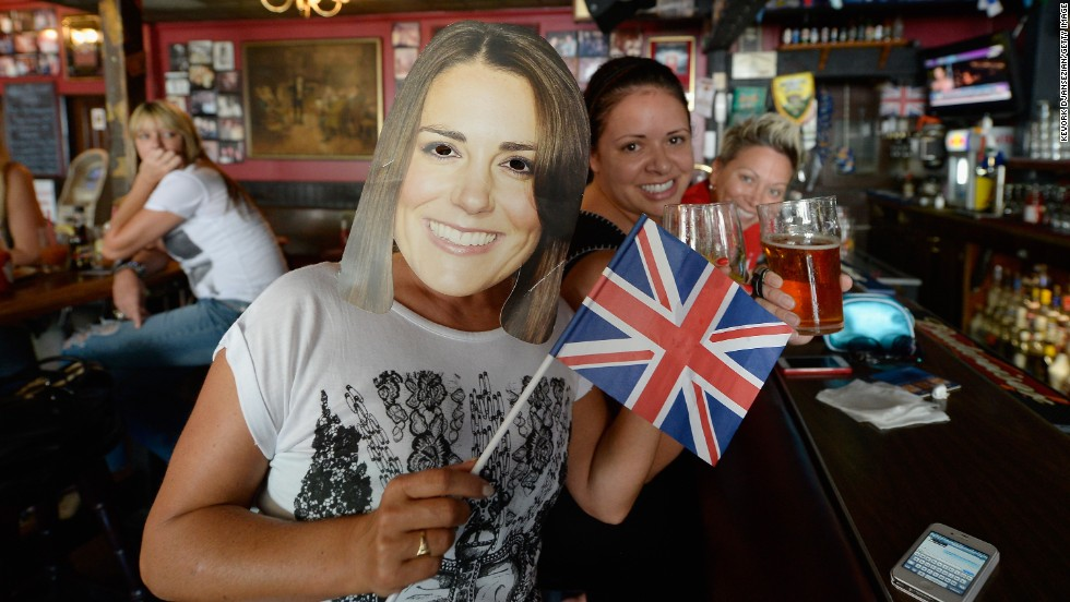 Karen Milne, left, of Scotland wears a mask of Catherine, Duchess of Cambridge, as she and friends celebrate the royal birth at Ye Olde King's Head English Pub in Santa Monica, California, on July 22.