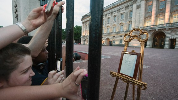 People clamor for their chance to see and photograph the birth announcement that was placed on a golden easel by the queen's press secretary on July 22.