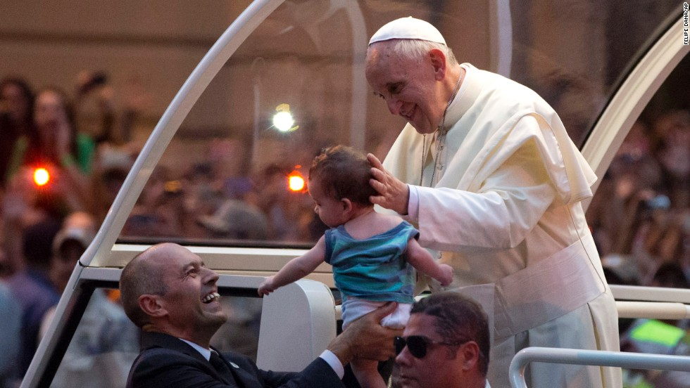 A member of the security detail holds up a baby for Pope Francis to kiss on July 22.