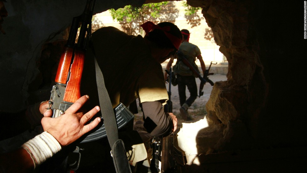 Free Syrian Army fighters move through a hole in a wall in Khan al-Assal on Monday, July 22, after seizing the town.