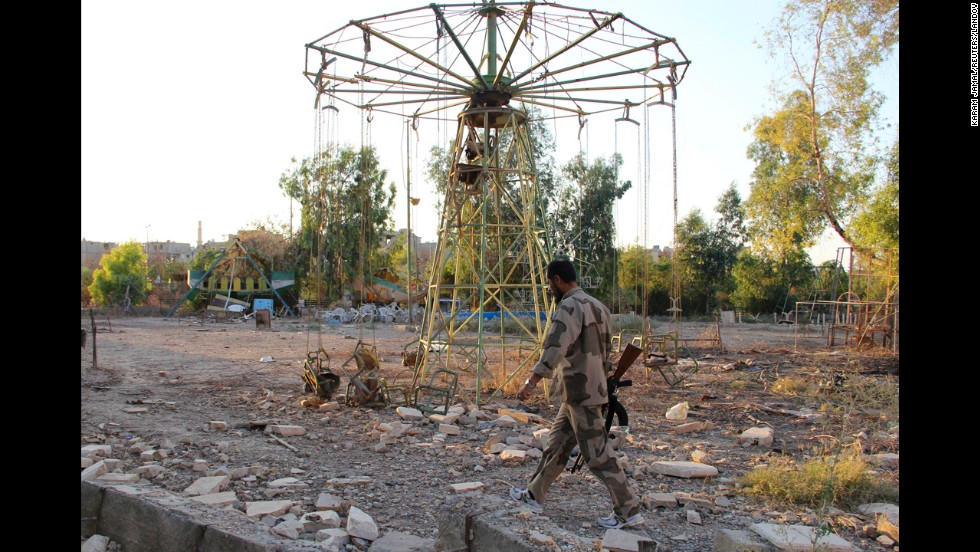 A rebel fighter walks past swings in a deserted playground in Deir al-Zor, Syria, on Sunday, July 21.