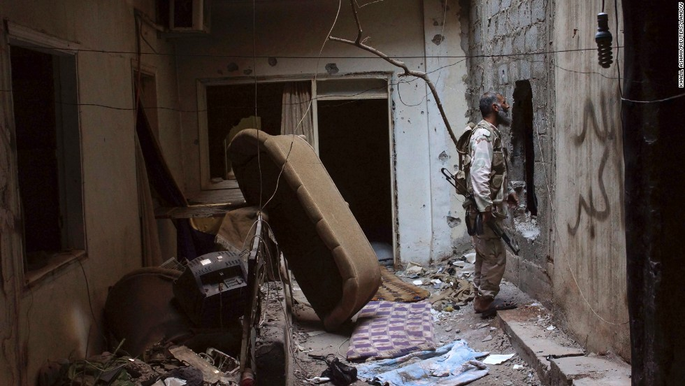 A rebel fighter speaks with a fellow fighter through a hole in a wall in Deir al-Zor on July 21.