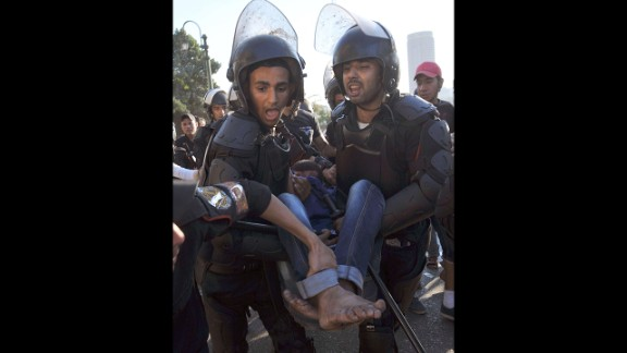 Riot police evacuate an injured anti-Morsy protester in Cairo on July 22.