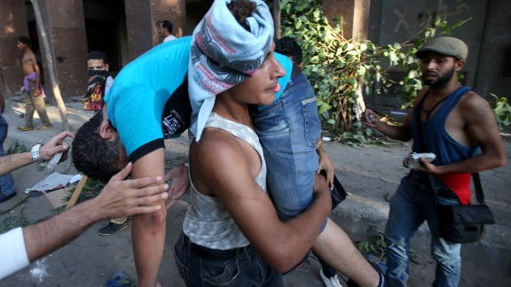 A Morsy opponent carries his injured friend in Cairo on July 22.