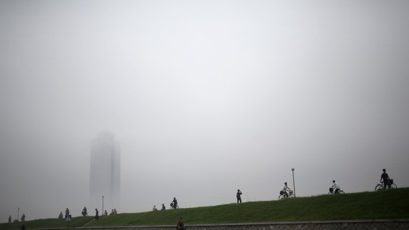 People make their way past a building clouded by a thick layer of mist on Monday, July 22, after torrential rain in Pyongyang, North Korea.