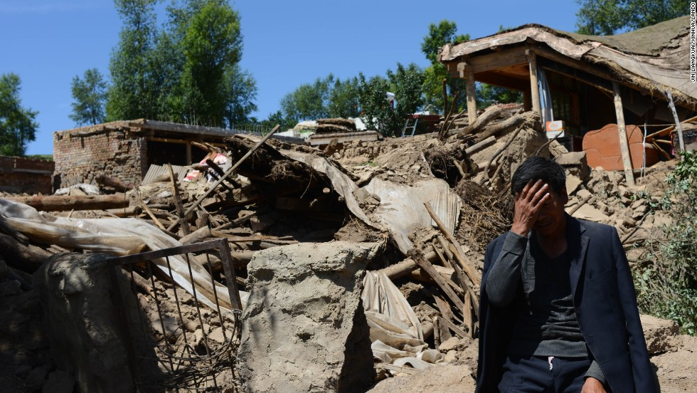 A man sits beside a collapsed house in Gansu province, in northwest China, on July 23.