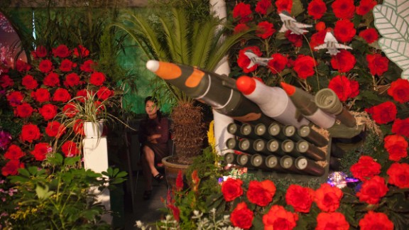 """A woman sits next to models of military weapons at a festival for the """"Kimilsungia"""" and """"Kimjongilia"""" flowers, named after the country"""