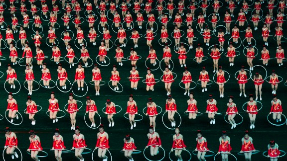 """Women jump through hula hoops during the opening night of the annual Arirang Festival, or """"mass games,"""" at Pyongyang"""