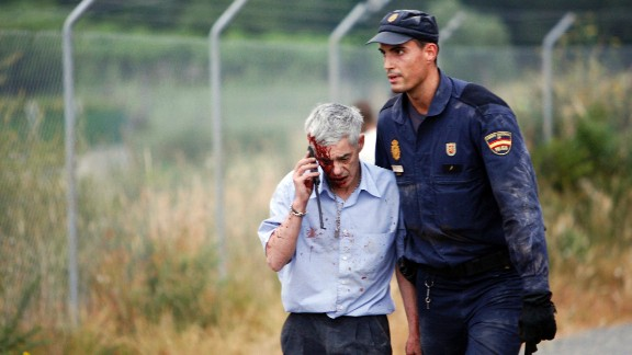 Train driver Francisco Jose Garzon, identified by Spanish newspapers El Pais and El Mundo, is helped from the scene by a police officer.