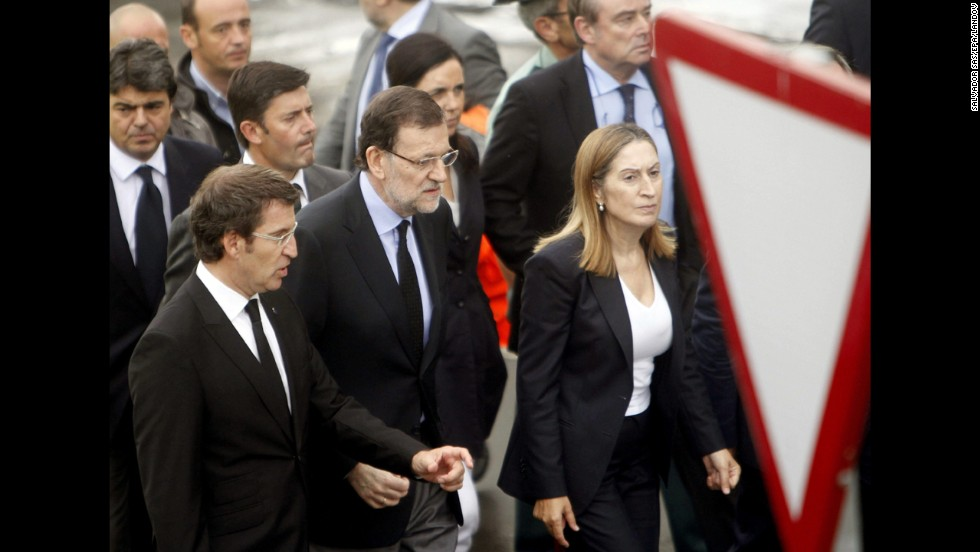 Spanish Prime Minister Mariano Rajoy, center, visits the crash site July 25 with Public Works Minister Ana Pastor, right, and Alberto Nunez Feijoo, head of the regional government in Galicia. The latter declared seven days of mourning for victims of the crash.<br />