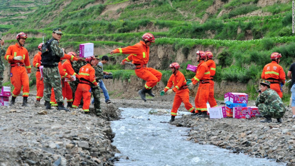 A rescuer  jumps over a creek as a team brings relief supplies for earthquake victims to Digu village on July 24.