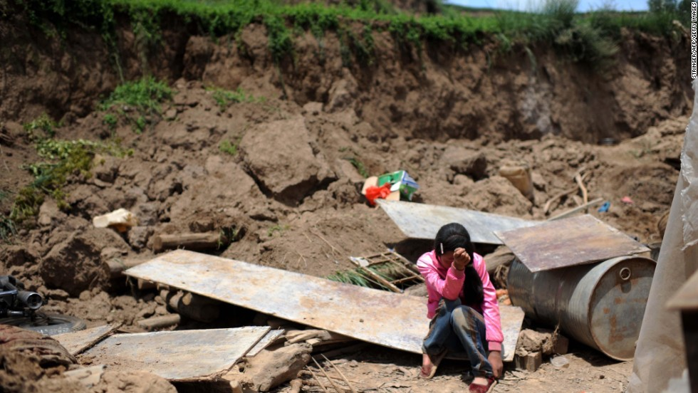 Song Xiaomei cries on Wednesday, July 24, after her home was destroyed by an earthquake in northwest China's Gansu province. The strong, shallow earthquake and powerful aftershocks jolted the region Monday morning.  The death toll is at 89, as of Friday, July 26.