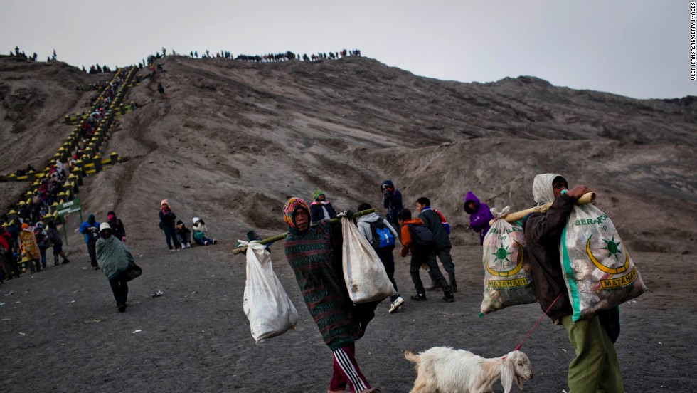Here, two villagers carry sacks full of offerings they managed to catch in their nets -- vegetables and even a live goat.