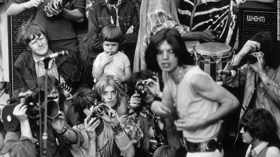 Jagger performs with the Rolling Stones in central London's Hyde Park in 1969. His then-girlfriend Marianne Faithfull watches from behind the photographers.