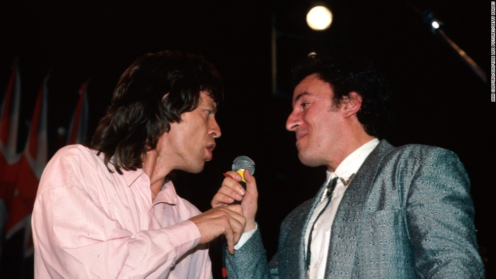 Mick Jagger and Bruce Springsteen share a microphone during the Beatles' induction into the Rock and Roll Hall of Fame in 1988.