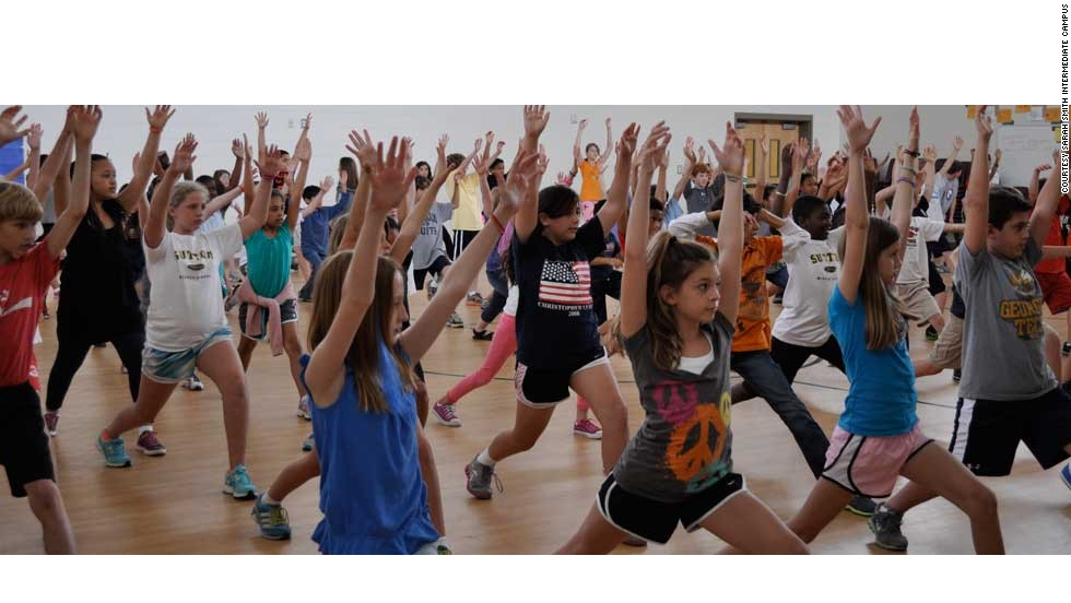 Students at Sandy Springs Middle School in Fulton County, Georgia, execute a high lunge pose. This exercise lengthens the spine, increases stamina and tones the legs.