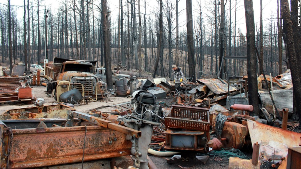 Alan Havens inspects his burned and rusty belongings on July 15. His mobile home and work equipment were lost in the fire.