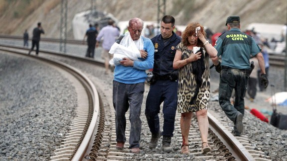 Injured people are evacuated at the site of the July 24 train accident. The driver of the train is being held, Spanish police said July 26.