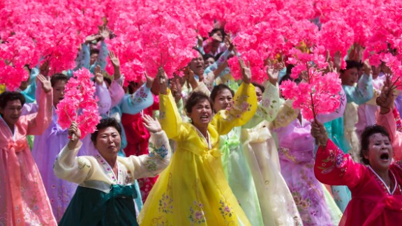 Women participating in the parade wave as they pass Kim Jong Un on July 27.