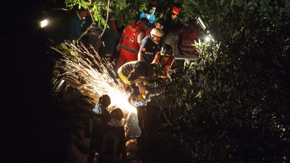 Sparks fly as firefighters cut into the wreckage.