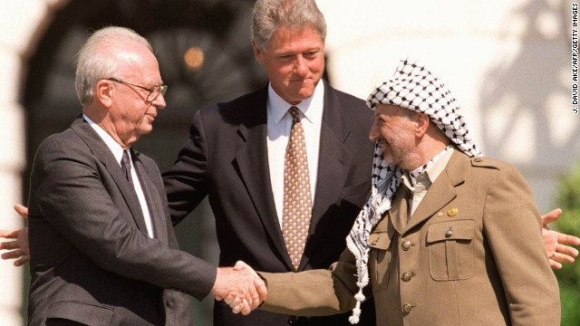 WASHINGTON, DC - US President Bill Clinton (C) stands between PLO leader Yasser Arafat (R) and Israeli Prime Minister Yitzahk Rabin (L) as they shake hands on September 13, 1993, at the White House in Washington DC. Rabin and Arafat shook hands for the first time after Israel and the PLO signed a historic agreement on Palestinian autonomy in the occupied territories. Photo credit J. DAVID AKE/AFP/Getty Images)