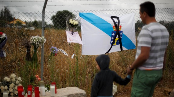 A man and child survey a memorial including a Galician flag on July 28.