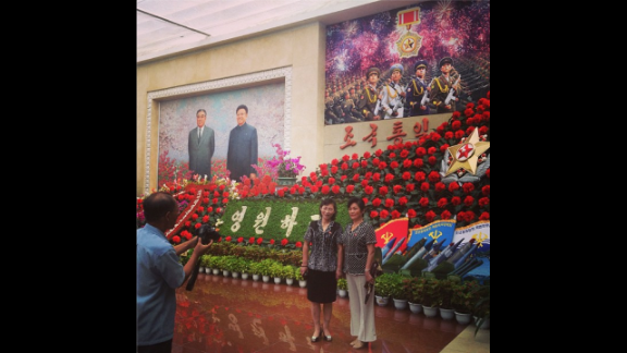 """""""This was most tightly controlled restricted foreign assignment of my career,"""" Watson said of his visit to the country. Here visitors take souvenir photos at the Kimilsungia and Kimjongilia flower festival. The flowers are named after former North Korean leaders Kim Il Sung and Kim Jong Il, who overlook the scene from the painting on the left hand side."""