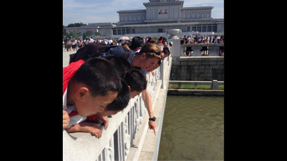 """Elsewhere, Watson enjoys a contemplative moment with North Korean schoolchildren enjoying the carp pools by the Kumsusan Palace of the Sun. """"[It was a] fascinating and strange experience,"""" Watson reflected of his time in the country."""